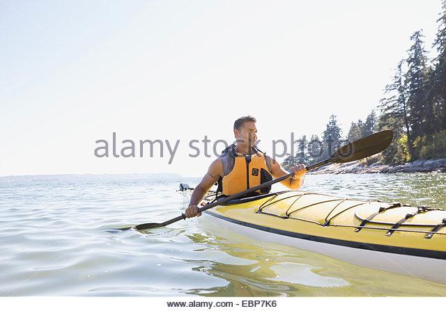 Man kayaking on sunny ocean - Stock Image