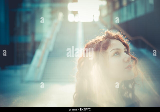 young beautiful hipster woman with red curly hair in the city - Stock Image