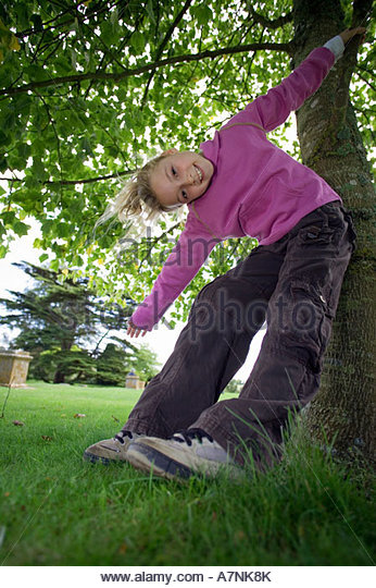 Girl 7 9 wearing purple top and combat trousers swinging from branch in garden arms outstretched head cocked smiling - Stock Image