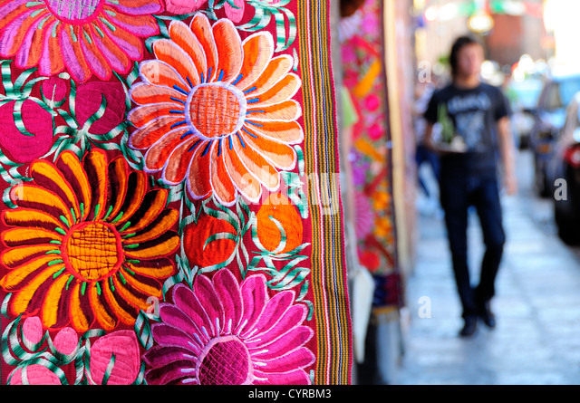 Mexico, Bajio, San Miguel de Allende, Brightly coloured embroidered floral textile hanging outside arts shop with - Stock-Bilder