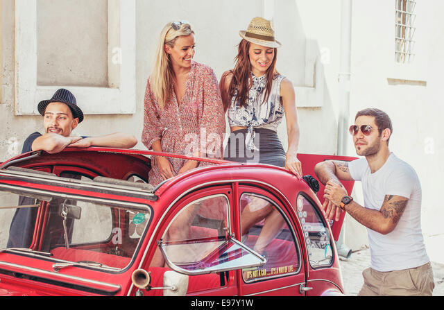 Young people preparing for road trip in vintage car - Stock Image