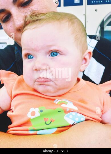 Close-Up Of Woman With Cute Blue Eyed Baby Girl - Stock Image