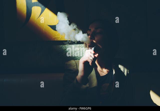 girl sits and smokes electronic cigarette - Stock Image