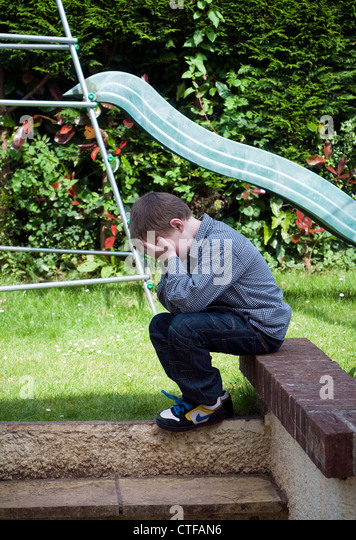 young boy in despair, relationships,Stress in trouble,Protests, Poverty,Loneliness,sibling rivalry,siblings - Stock Image