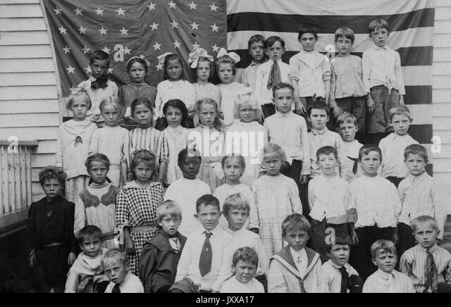 Full length landscape shot of schoolchildren in front of an American flag, one African American girl in the second - Stock Image