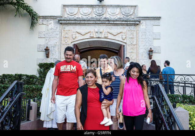 Florida Miami Beach St. Francis De Sales Catholic Church members after service leaving Hispanic man woman baby family - Stock Image