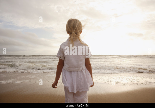 Girl looking out at ocean - Stock Image