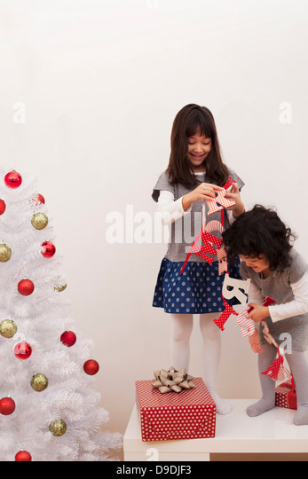 Two girls preparing for Christmas, putting up a Christmas banner - Stock Image