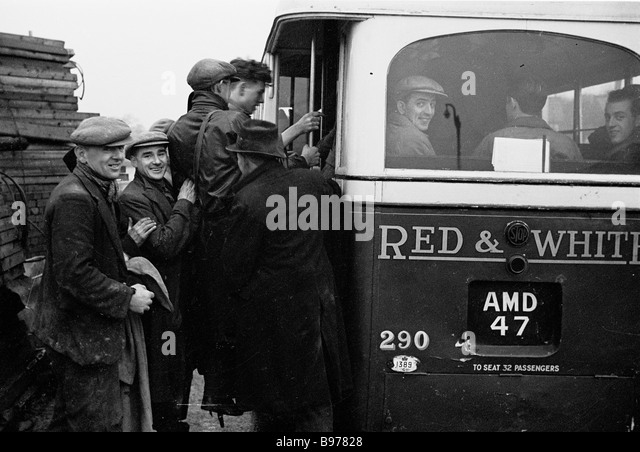 Group of workmen from the paper factory at Trehafod, South Wales getting onto a bus after finishing a day's - Stock Image