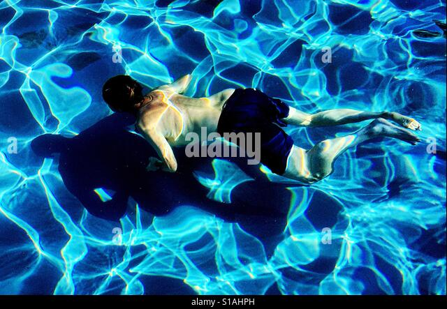 A man swimming underwater with bigger shadow below and reflective patterns created by the sun shining on the water. - Stock-Bilder
