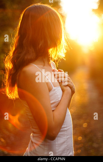 Beautiful young girl with long hair and white dress looking towards the golden light of the setting sun with hands - Stock-Bilder