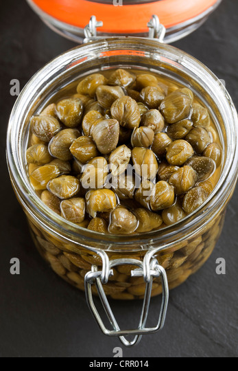 Capers in Glass Storage Jar - Stock Image