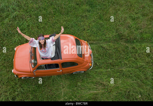 Hippy female stretching out of car - Stock Image