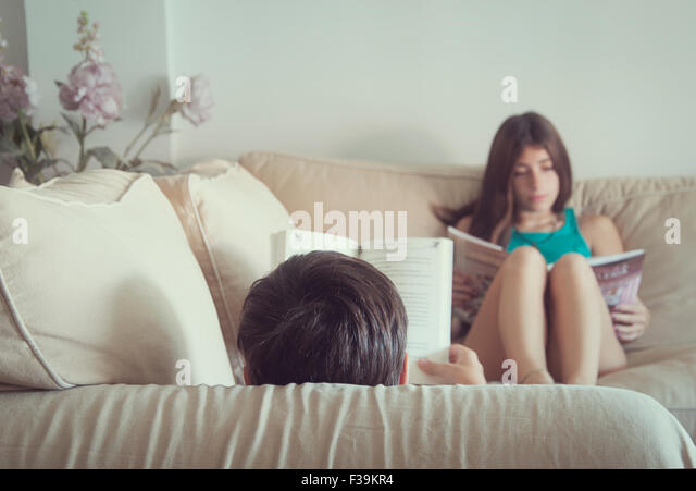 Teenage boy and girl sitting in the sofa reading books - Stock Image