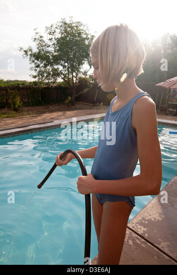 Ten year old girl pouring water into a swimming pool from a hose. - Stock Image