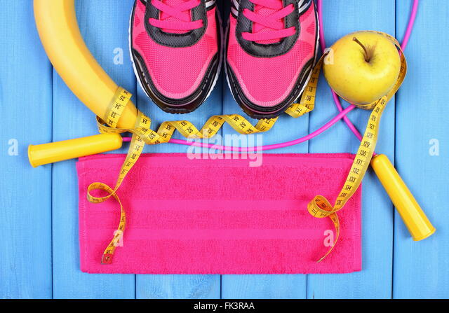 Pair of sport shoes, fresh fruits and accessories for fitness or sport on blue boards, healthy and active lifestyles, - Stock-Bilder