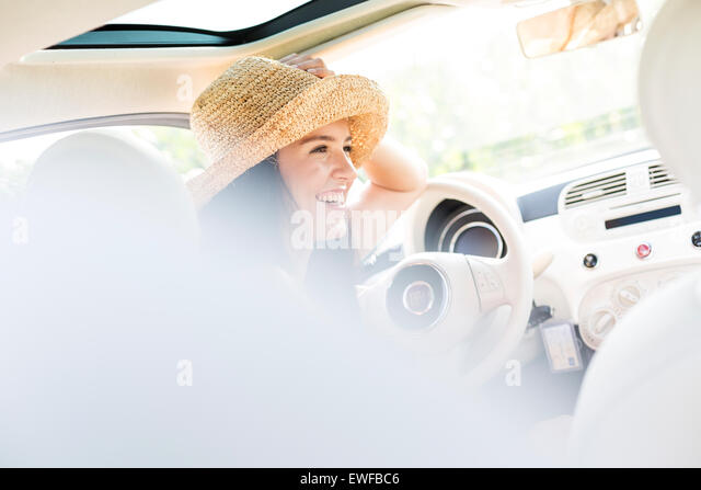 Happy woman sitting in car - Stock Image