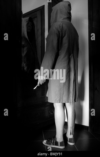 Hooded woman with knife in front of the mirror - Stock Image