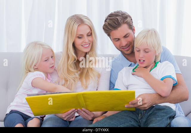 Happy family reading a story together - Stock Image