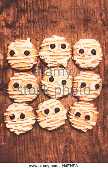 Frightening kitchen foods with mummy white choc short-bread decorations looking fearful on wooden backdrop. Halloween - Stock Image