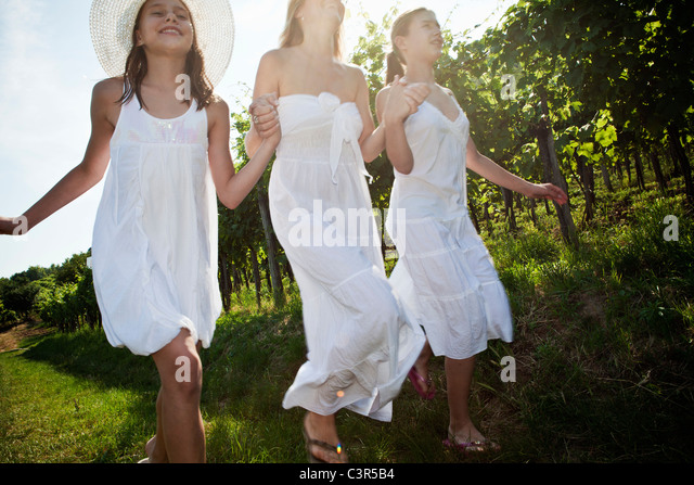Mother and daughters running in vineyard - Stock Image