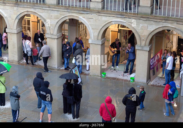 People listening to live music at the Piece Hall, Halifax, West Yorkshire - Stock Image