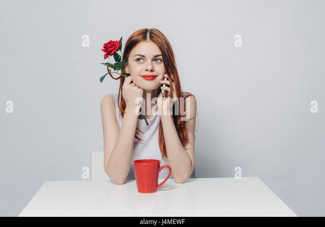 Caucasian woman sitting at table holding rose talking on cell phone - Stock-Bilder