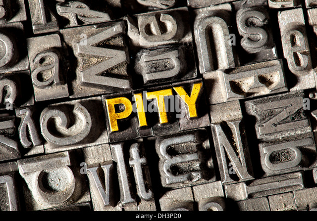 Old lead letters forming the word PITY - Stock Image