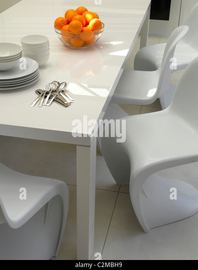 House in Chelsea, London. Modern white dining table with cantilevered white moulded chairs and white floor - Stock-Bilder