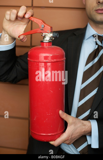 Businessman holding a fire extinguisher - Stock Image