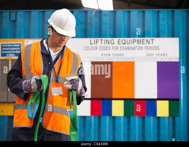 Worker examining safety rope on site - Stock Image