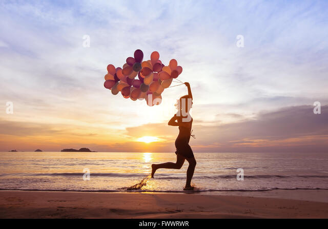 happiness concept, psychology of happy people, young woman running with multicolored balloons on the beach - Stock Image