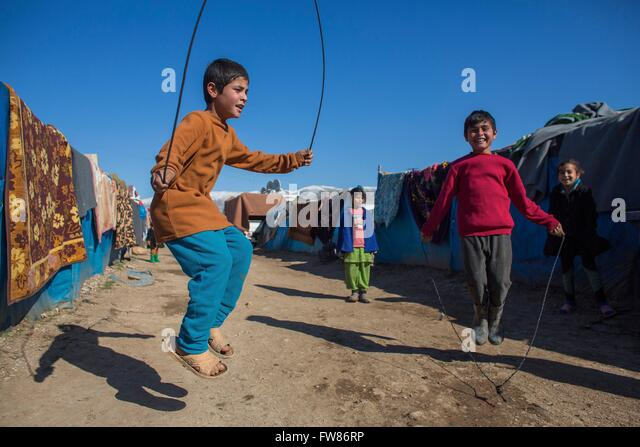 children jumping rope in a refugee camp in Northern Iraq - Stock Image
