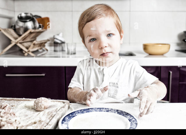 Baby boy preparing meatballs. He is looking straight to the camera - Stock Image