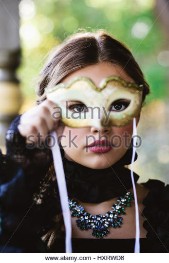 Young woman holding a masquerade mask in front of her face - Stock Image