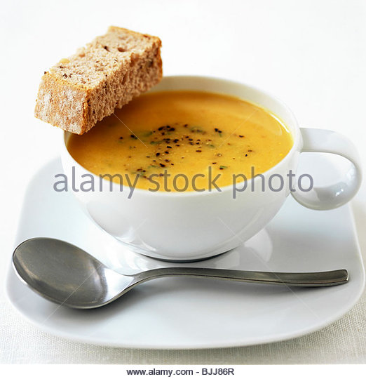 Parsnip soup in a soup cup with a piece of bread - Stock Image