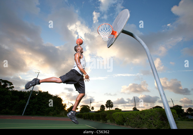 male making slam dunk at outdoor basketball goal - Stock Image