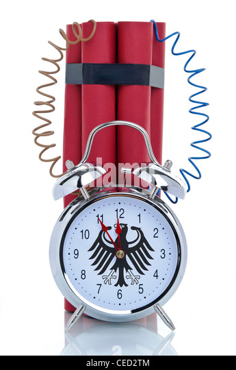 Time bomb, alarm clock with attached dynamite sticks and the Germany's Federal Eagle on its clock-face - Stock Image