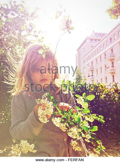 Low Angle View Of Girl Looking At Plant On Sunny Day - Stock Image