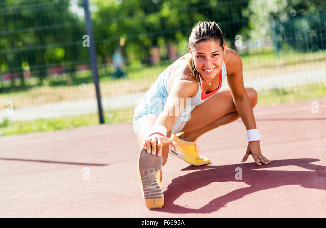 Beautiful young athletic woman stretching in summer before running - Stock Image