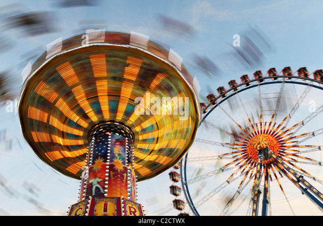 A spinning carousel and the big wheel, part of the Oktoberfest funfair set up every autumn on the Theresienwiesen - Stock Image