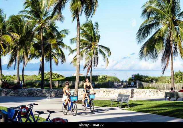 Miami Beach Florida Lummus Park woman friends biking riding bicycles bike share Citi - Stock Image