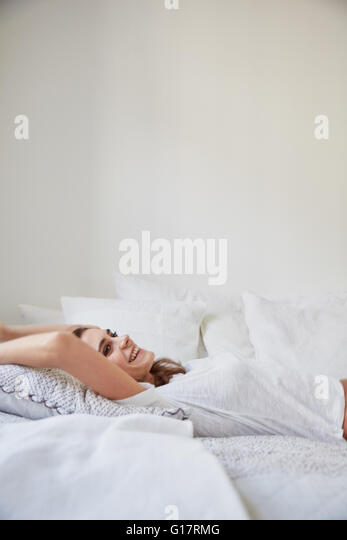 Surface view of beautiful young woman lying back on bed - Stock Image