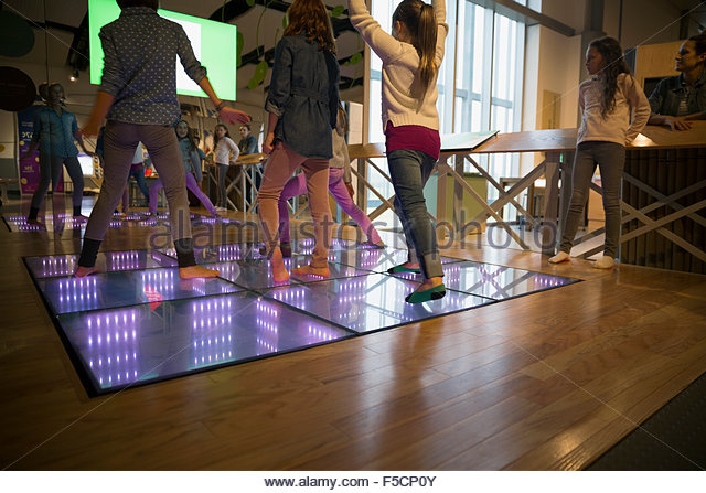 Girls dancing on illuminated floor at science center - Stock Image