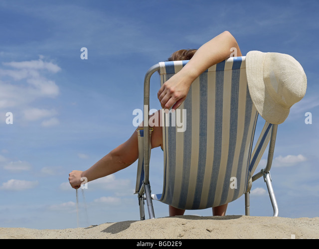 Woman relaxing on the beach on deckchair playing with sand - Stock Image