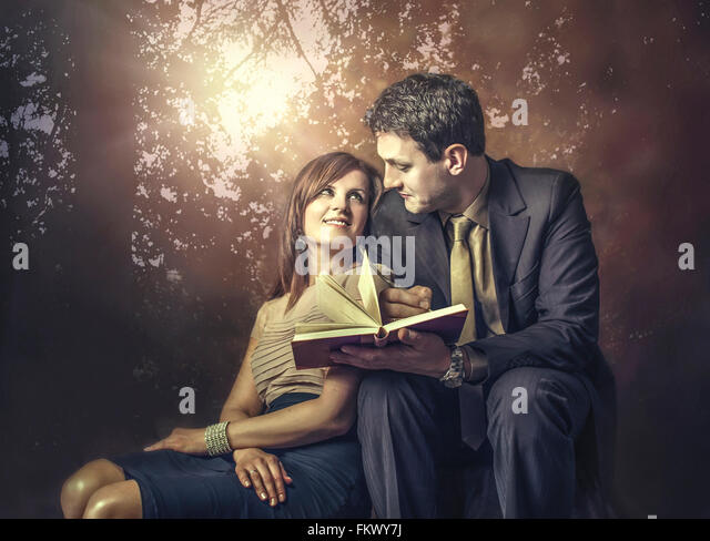 young couple in love sitting in park - Stock Image