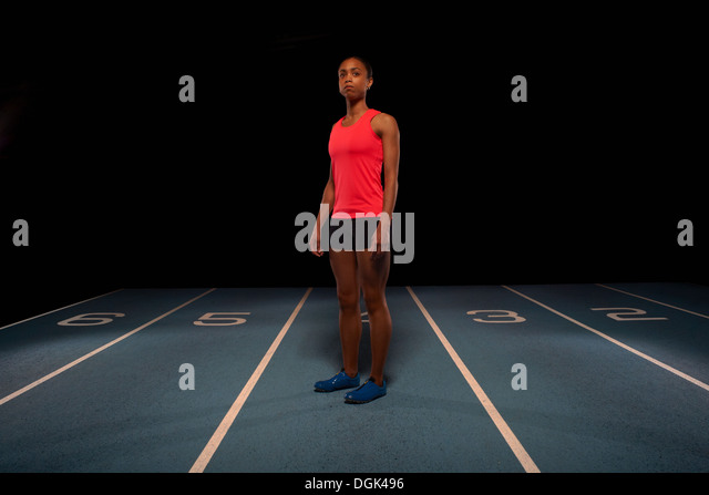 Young female athlete standing on race track - Stock Image