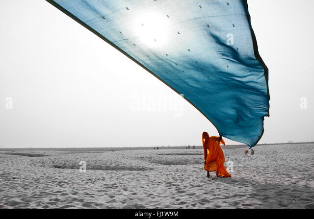Indian hindu woman with saree on the banks of the ganges, in the sand - Stock Image