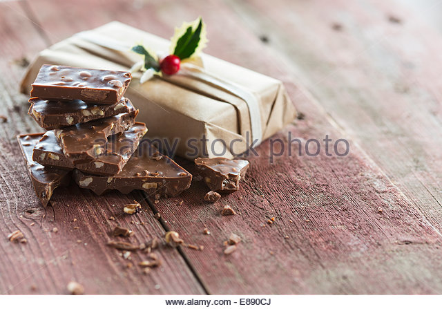 Pieces of chocolate candy bar near Christmas gift - Stock Image