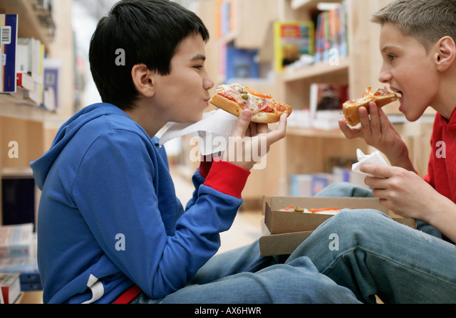 Two boys eating pizza inside a library, fully_released - Stock Image